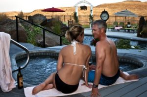 Swimming pool, patio area in the distance; couple enjoying the hot tub in the foreground