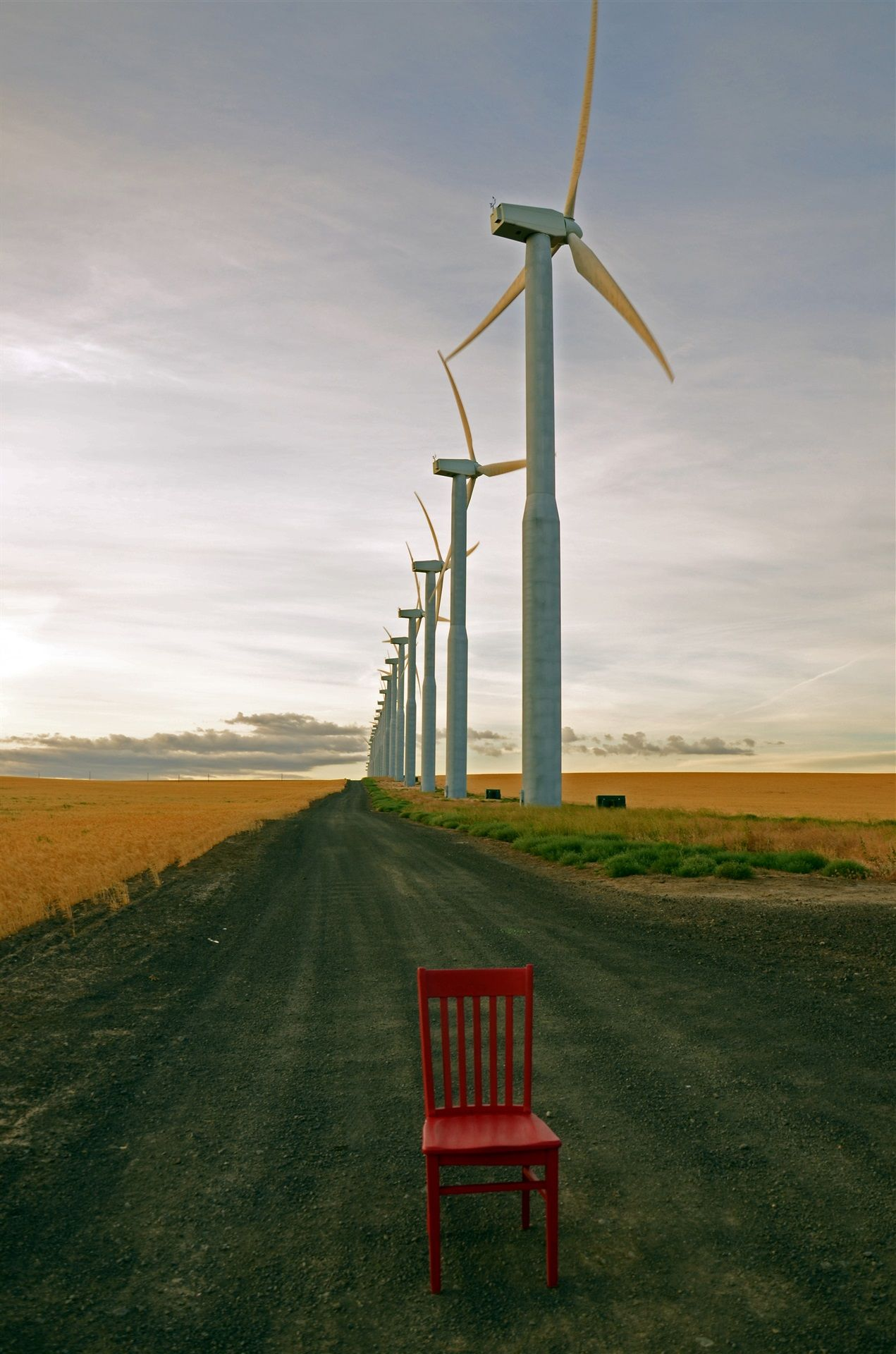 Red chair sitting on a gravel road that is lined with wind turbines